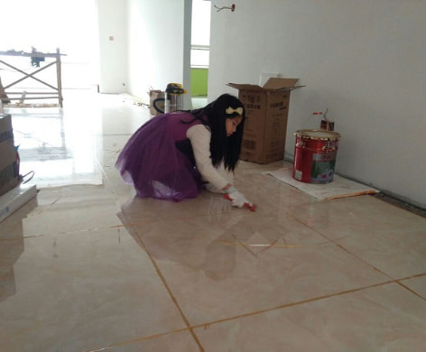 This is Ms. Peng's daughter is helping to remove the extra tile grout with a scraper.
